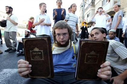 Un jeune juif orthodoxe brandissant le livre