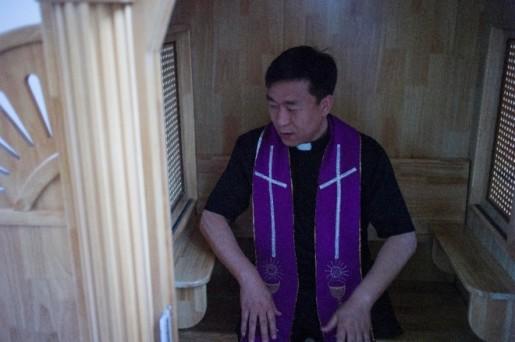 Le père Lin Xiuqiang pose dans sa toute nouvelle église à Tianjin