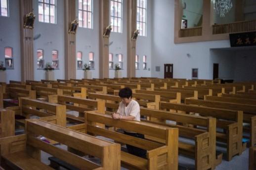 Une femme chinoise prie dans l'église flambant neuve de Tianjin